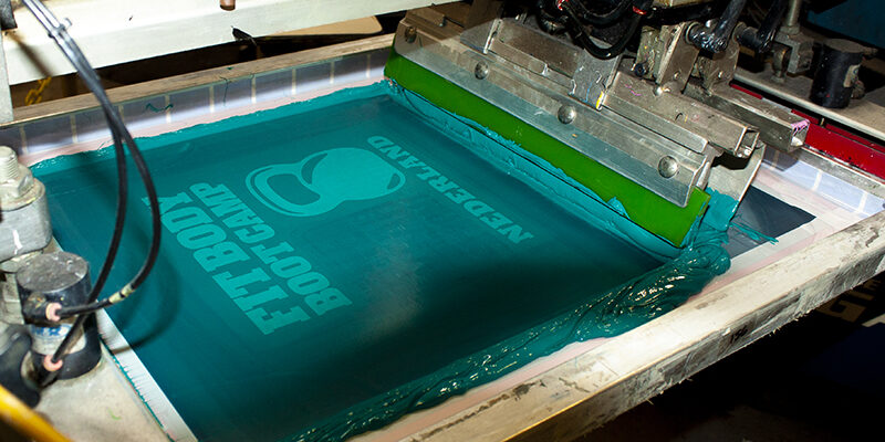 fitbody Boot Camp screen being printed on tshirts with with teal ink on screen